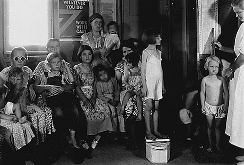 Photograph of Arvin Camp parents with children, who are having height and weight measured, 09/1936, courtesy of the US National Archives.