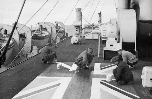 Lascars painting a Union flag on the deck of the P&O liner 'Chitral' (National Maritime Museum Photographic Collections).